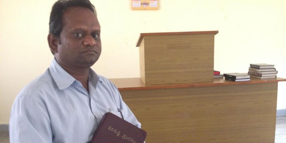 Chadamla, who later changed his name to Samuel, holding his Bible in a chapel at the headquarters of the Adventist Church's South Andhra Section in Ibrahimpatnam, India. (Andrew McChesney / Adventist Mission)