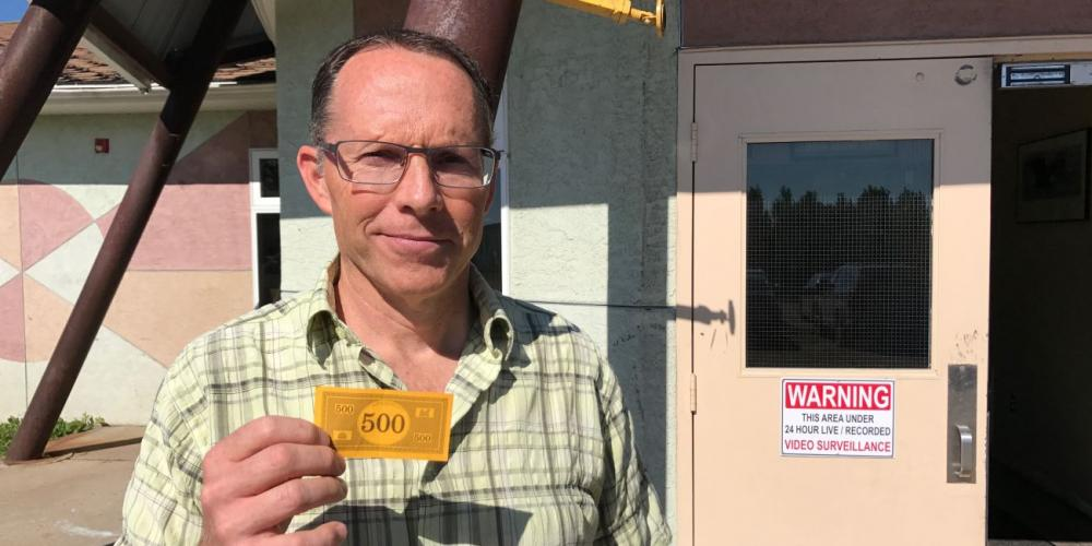 Guidance counselor Kelly Stickle holding the $500 that Charlize gave him outside Mamawi Atosketan Native School in Alberta, Canada. (Andrew McChesney / Adventist Mission)