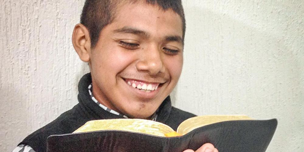 Uriel Arodi Albino Ramos, 15, holding his Bible as he shares his story. Five people have been baptized through his Bible studies. (Andrew McChesney / Adventist Mission)