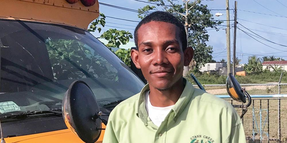 Angel Sabal, 24, standing near a school bus in Dangriga Town, Belize. (Andrew McChesney / Adventist Mission)