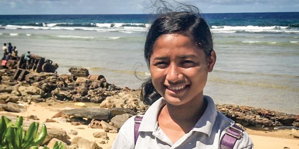 Viona Boro, 16, standing on a Pacific Ocean beach on Ebeye Island. (Andrew McChesney / Adventist Mission)