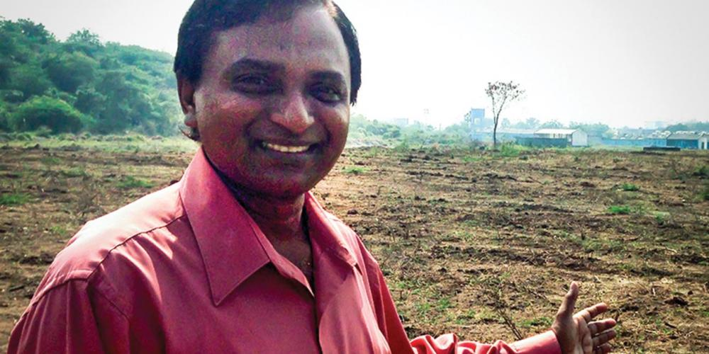 Vara Prasad Jacob, president of the South Andhra Section, showing the land where the center will be built. (Andrew McChesney / Adventist Mission)