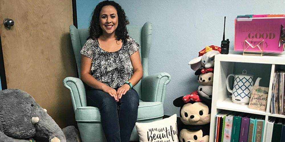 Giselle Ortiz, 27, case manager at Holbrook Indian School, posing in the chair in her office where students usually sit. (Andrew McChesney / Adventist Mission)