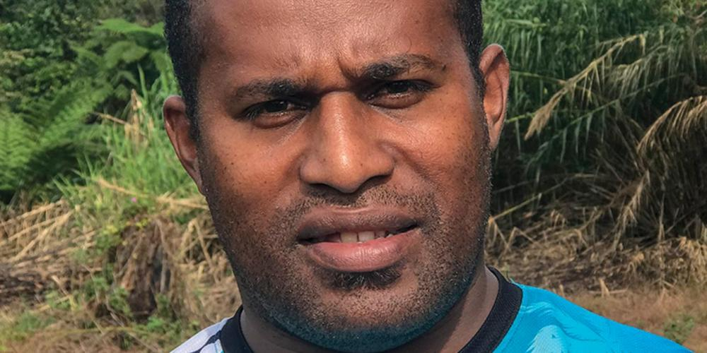 Kositela Tito, 33, standing near the open-air Seventh-day Adventist church just outside his father's home village, Nakavika, in Fiji. Villagers, who belong to another Christian denomination, reluctantly allowed the church to be built after the death of Tito's father but only outside the village.